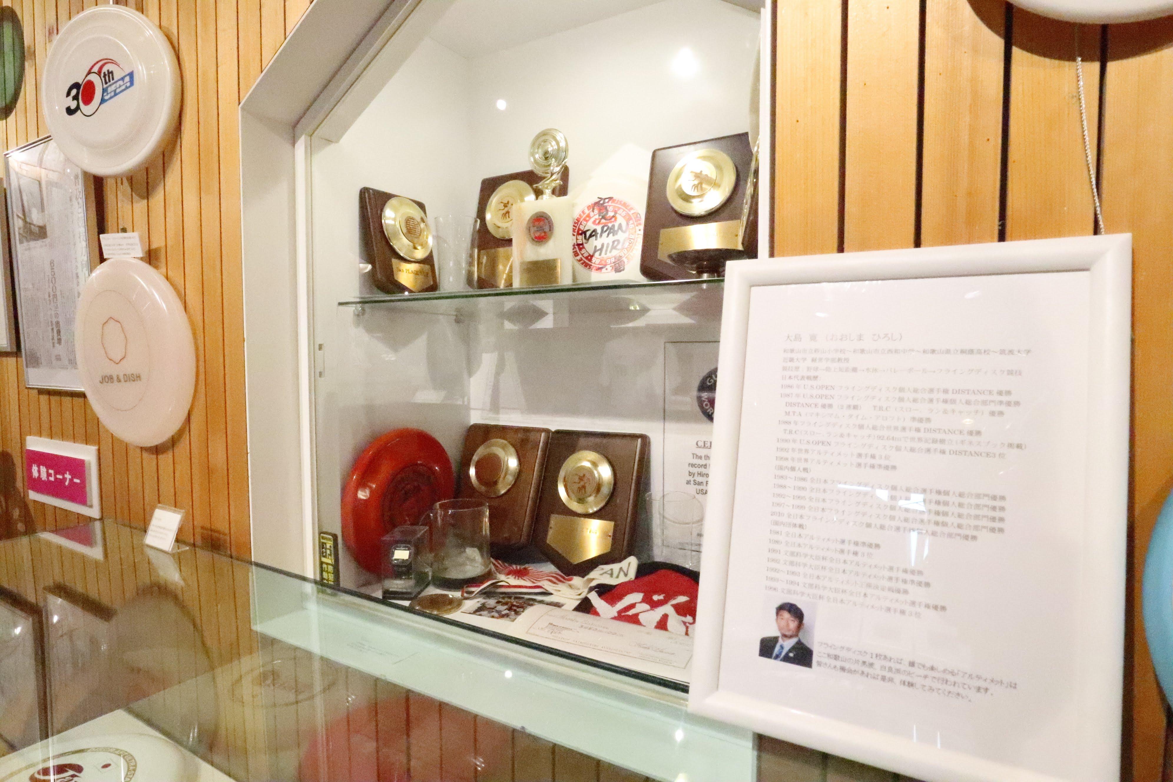 大島寛氏の紹介パネルと氏がこれまで獲得してきたメダルなど